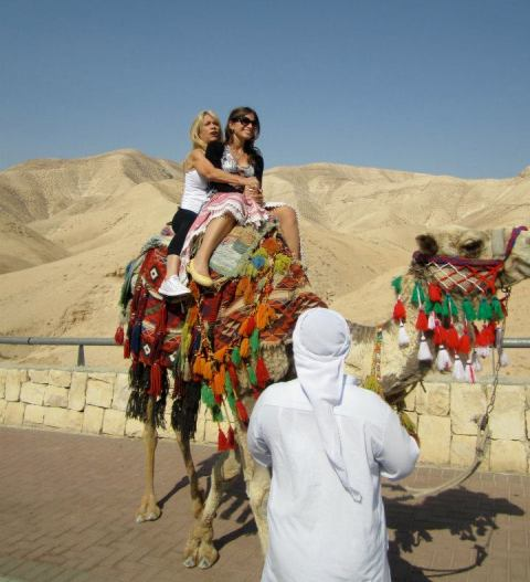 Lindsay riding a camel in Israel with her mother