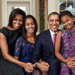 Malia Obama sits in between her mother and father